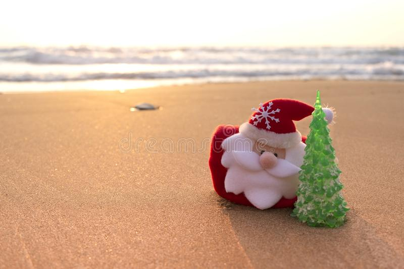 Santa Claus and Christmas tree on the beach or sandy sea shore. Christmas and New Year celebration travel concept. stock photography