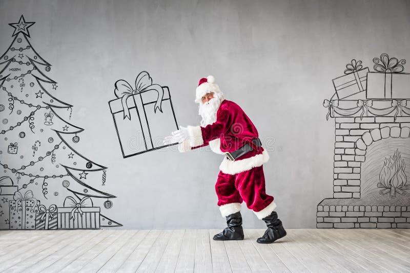 Santa Claus Christmas Xmas Holiday Concept. Santa Claus holding gift box. Christmas Xmas holiday concept stock photography