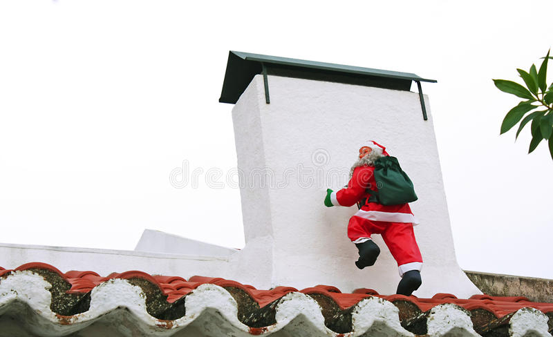 Santa Claus climbing the chimney royalty free stock photos