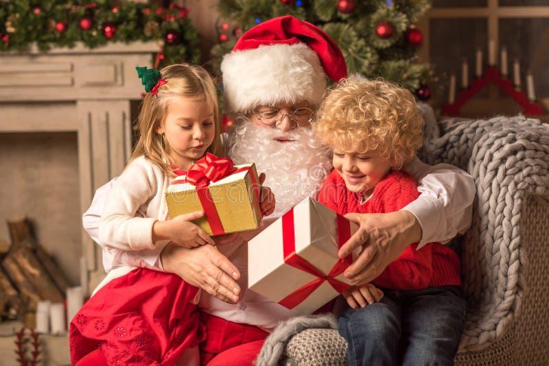 Santa Claus com as crianças que guardam caixas de presente imagens de stock