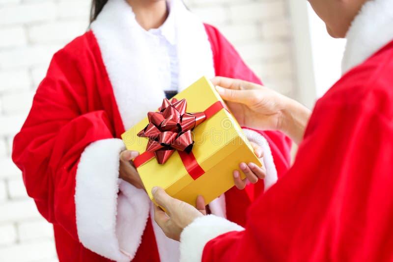 Santa Claus com a caixa de presente que dá um atual de Natal a ela, Mer fotografia de stock