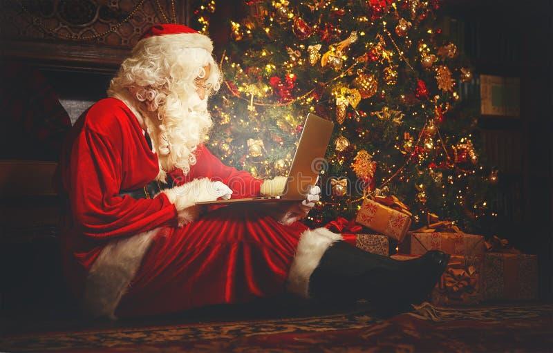 Santa Claus com o computador antes do Natal imagens de stock