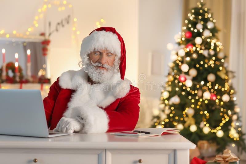 Santa Claus com o portátil que senta-se na tabela na sala decorada para o Natal fotografia de stock