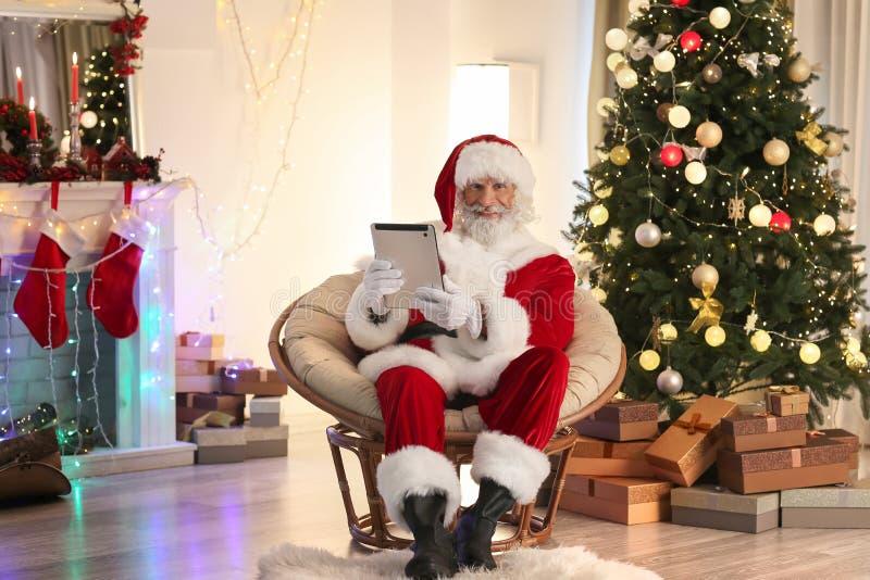 Santa Claus com o tablet pc na sala decorada para o Natal imagens de stock