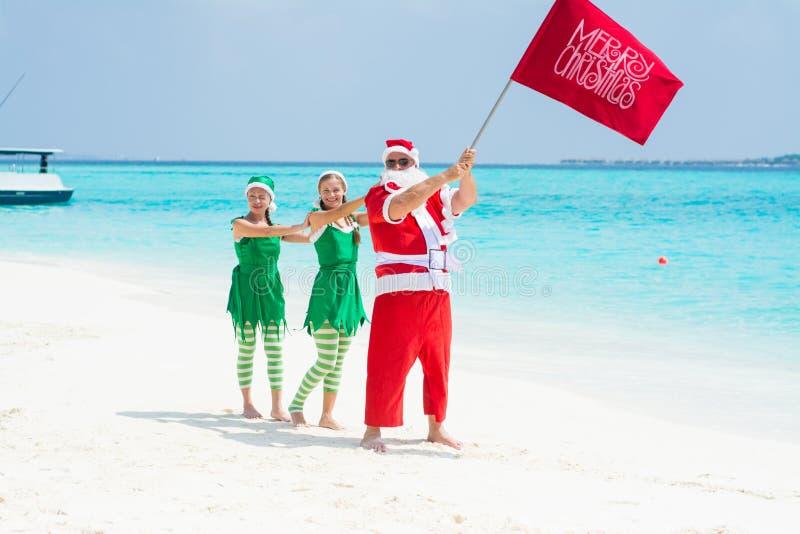 Santa Claus com os elvs que guardam a bandeira do Feliz Natal imagem de stock