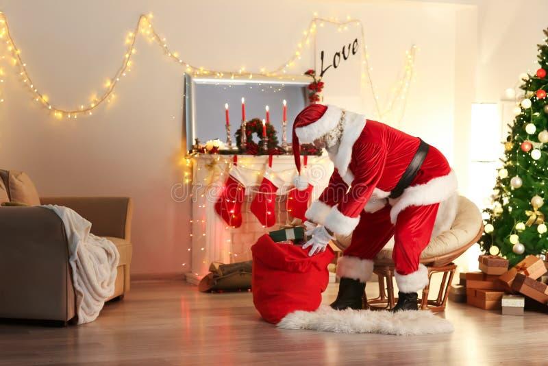 Santa Claus com saco completamente dos presentes na sala decorada para o Natal foto de stock royalty free