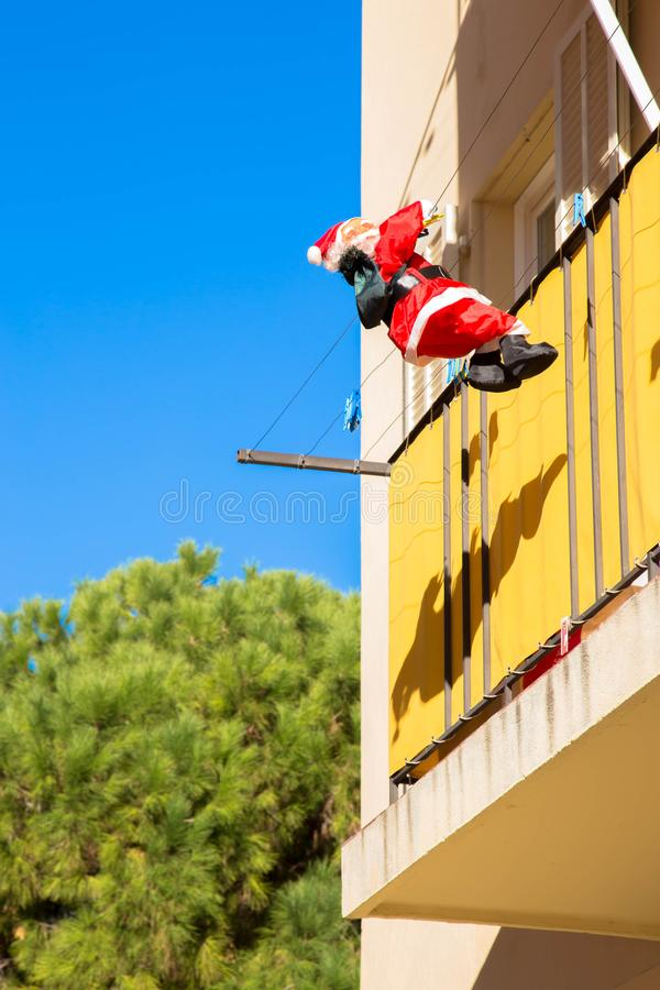 Santa Claus com saco dos presentes está escalando a parede da casa fotos de stock royalty free