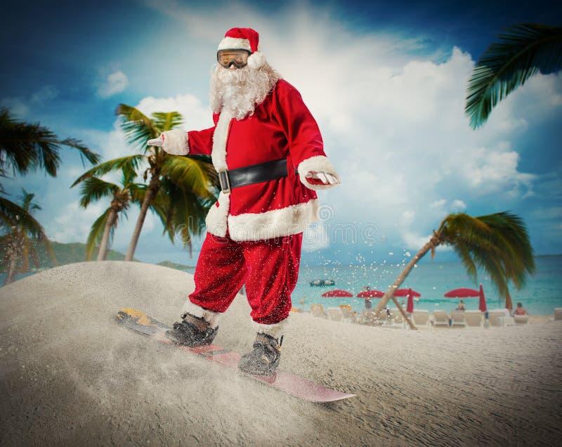 Santa Claus com snowboard em uma praia foto de stock
