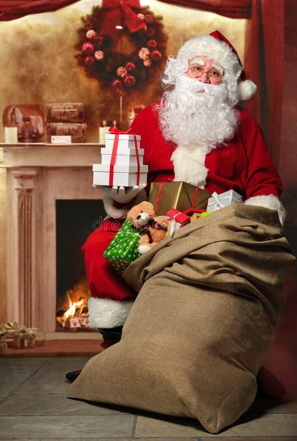 Santa Claus com um saco dos presentes na chaminé foto de stock royalty free