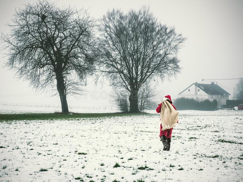 Santa Claus with a large sack of gifts walking in winter landscape. Happy Christmas consept. stock photography