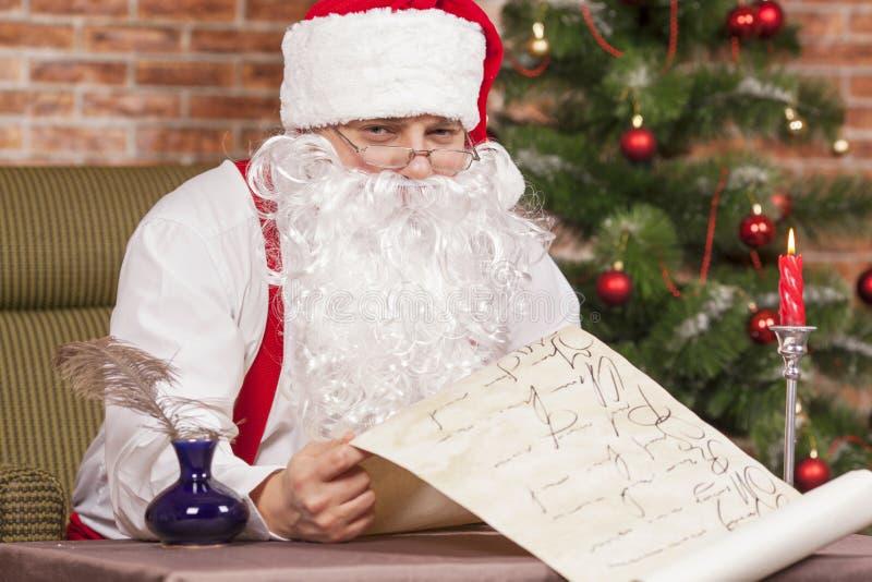 Santa Claus comprueba su lista foto de archivo