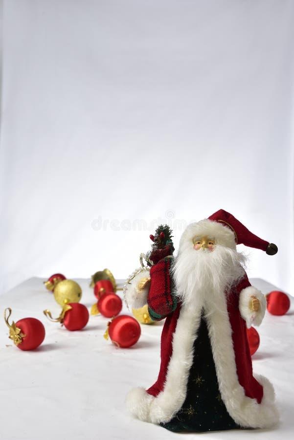 Santa Claus con coloridas bolas de Navidad en el suelo sobre fondo blanco imagen de archivo libre de regalías
