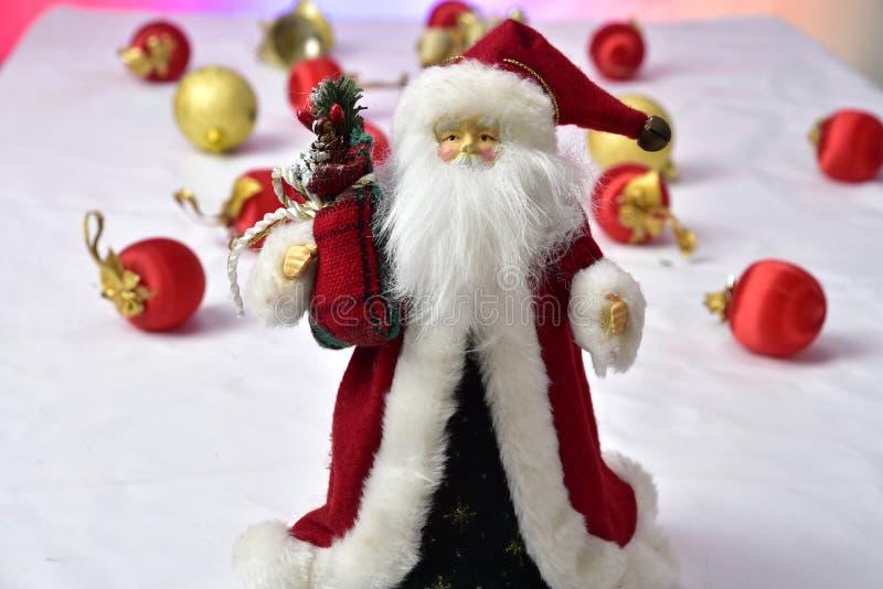 Santa Claus con coloridas bolas de Navidad en el suelo sobre fondo blanco fotos de archivo