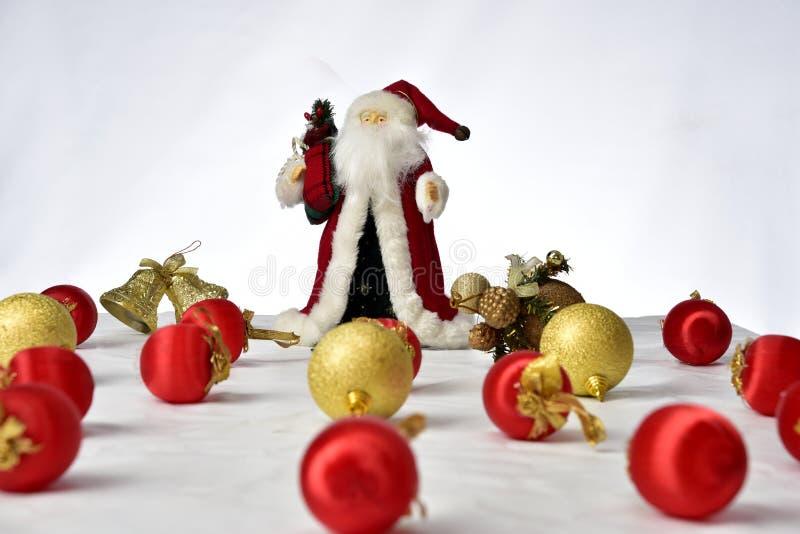 Santa Claus con coloridas bolas de Navidad en el suelo sobre fondo blanco imagen de archivo