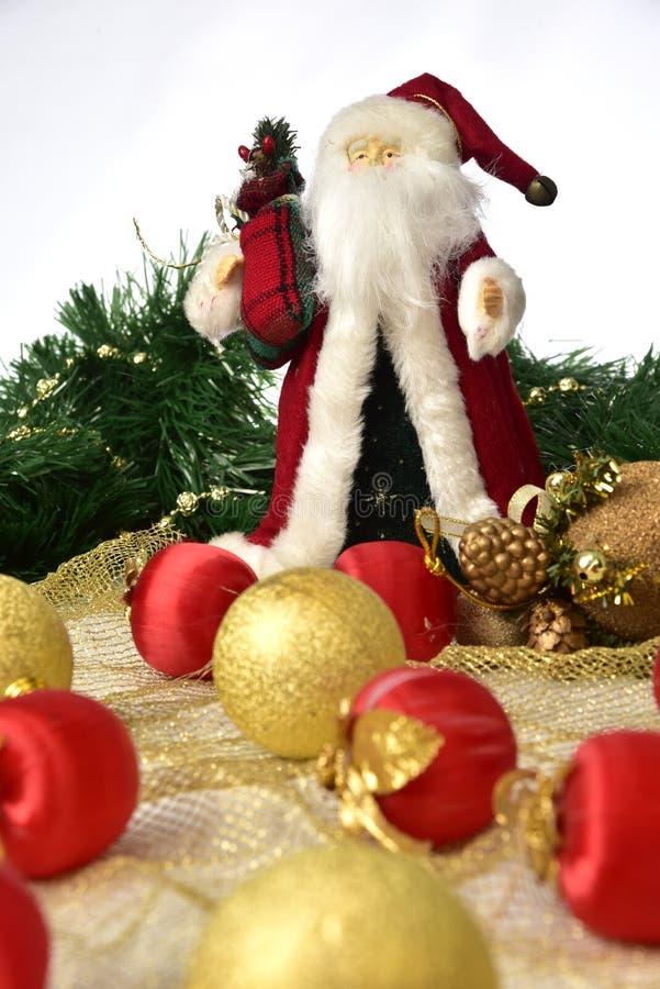 Santa Claus con coloridas bolas de Navidad en el suelo sobre fondo blanco fotos de archivo libres de regalías
