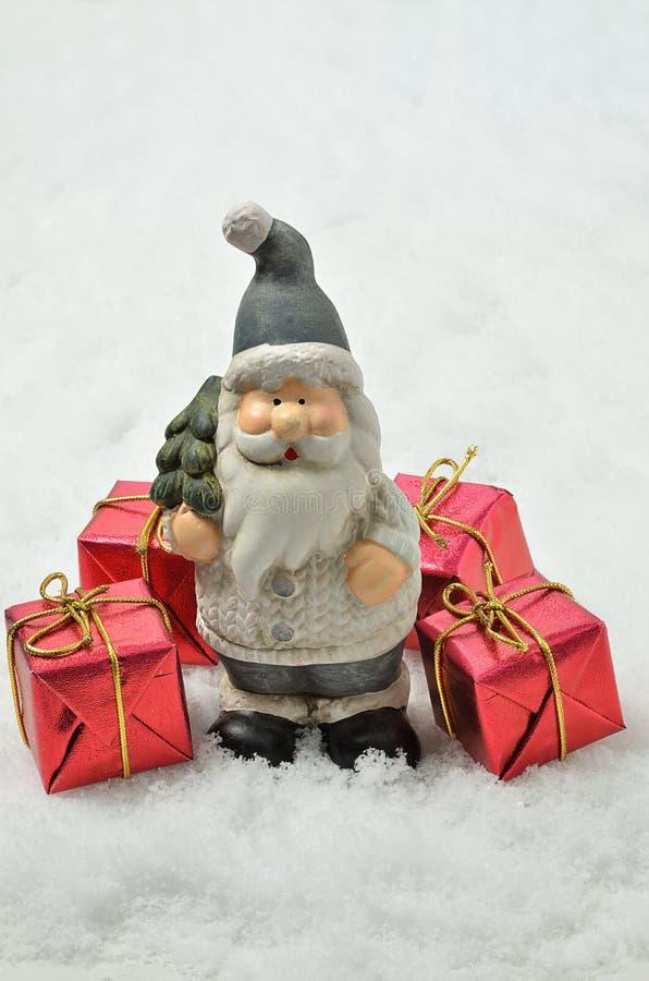 Santa Claus con cuatro paquetes rojos en el fondo de la nieve, vertical imagenes de archivo