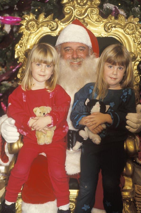 Santa Claus con dos niñas, Santa Monica, California imagenes de archivo
