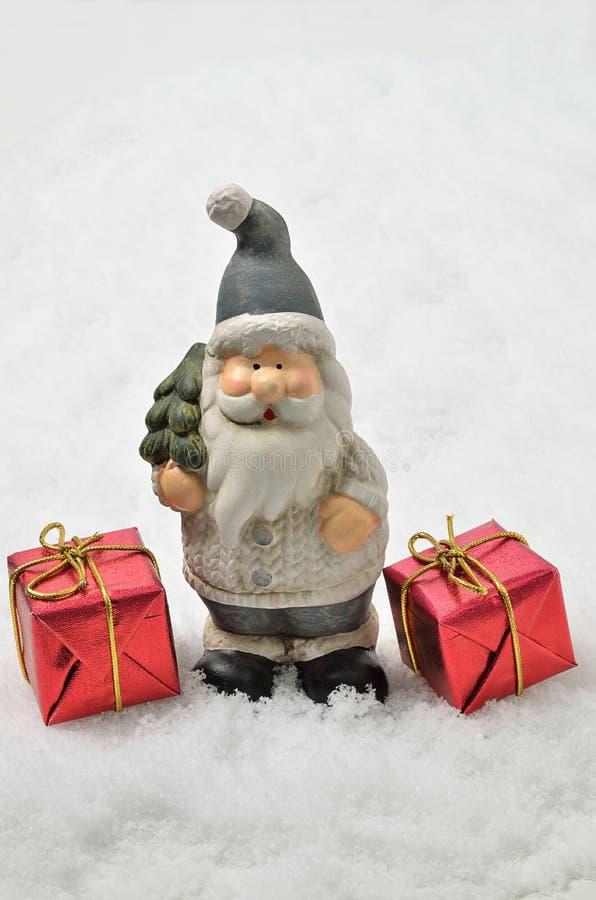 Santa Claus con dos paquetes rojos en el fondo de la nieve, vertical imagen de archivo libre de regalías