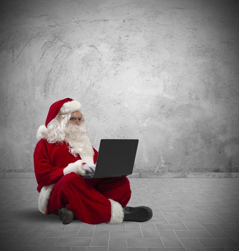 Santa Claus con el ordenador portátil foto de archivo