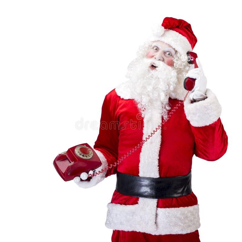 Santa Claus con el teléfono rojo que presenta en blanco imagenes de archivo