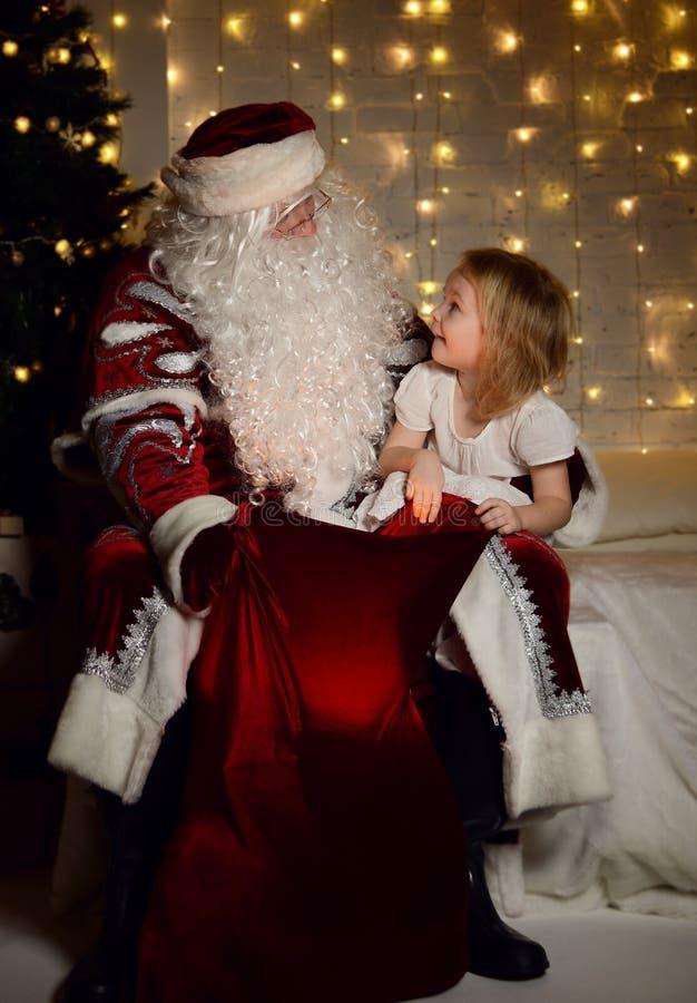 Santa Claus con i piccoli bambini svegli felici ragazzo e ragazza vicino all'albero di Natale immagini stock