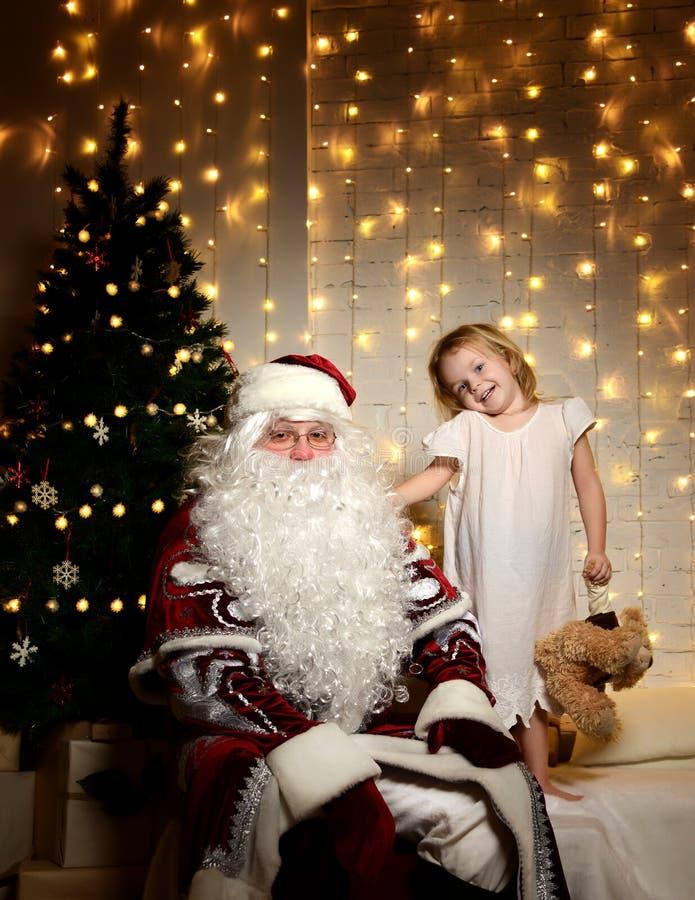 Santa Claus con i piccoli bambini svegli felici ragazzo e ragazza vicino all'albero di Natale immagini stock libere da diritti