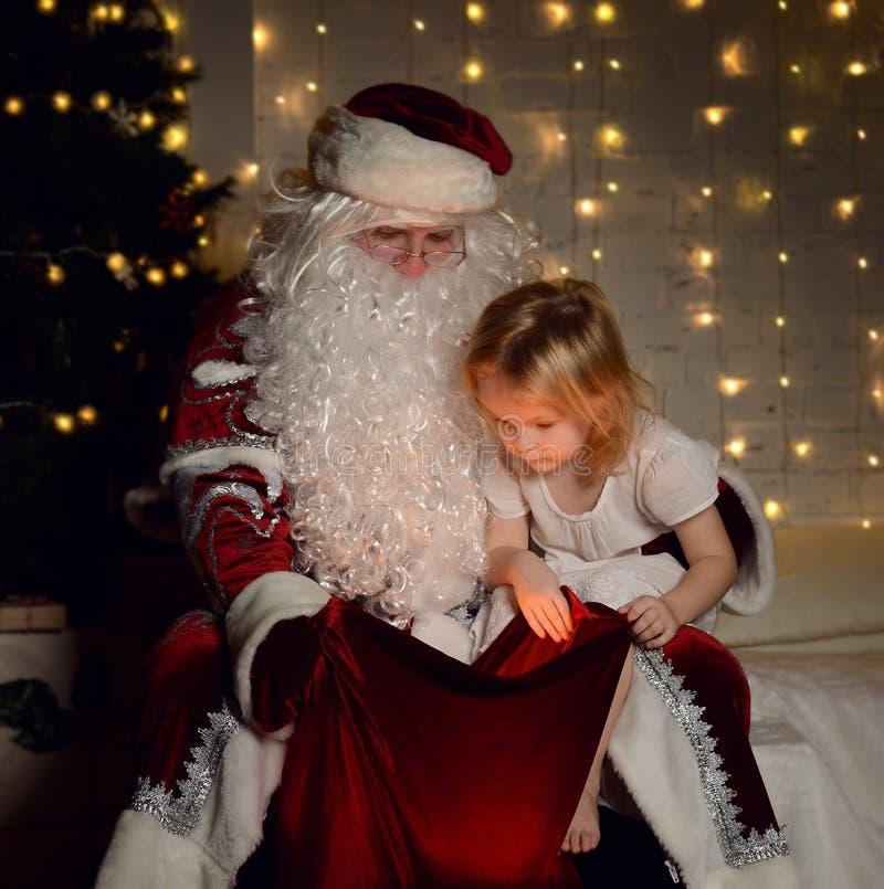 Santa Claus con i piccoli bambini svegli felici ragazzo e ragazza vicino all'albero di Natale fotografia stock