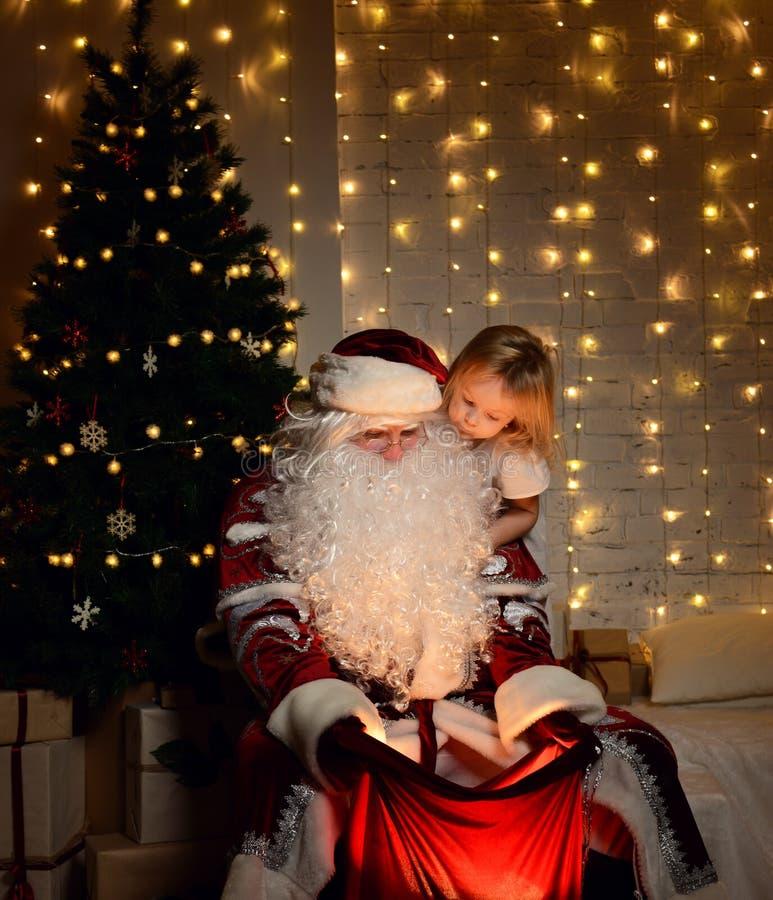 Santa Claus con i piccoli bambini svegli felici ragazzo e ragazza vicino all'albero di Natale fotografia stock libera da diritti