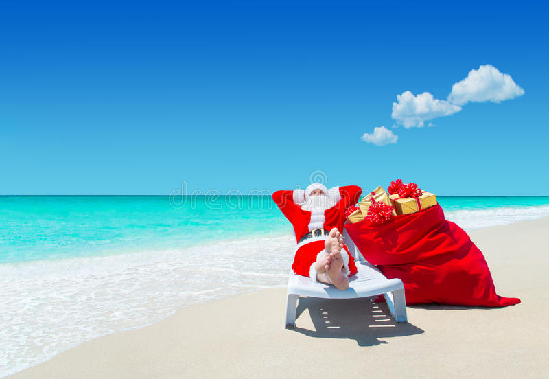 Santa Claus con il sacco di Natale in pieno dei regali si rilassa a piedi nudi su sunlounger alla spiaggia sabbiosa perfetta dell fotografia stock
