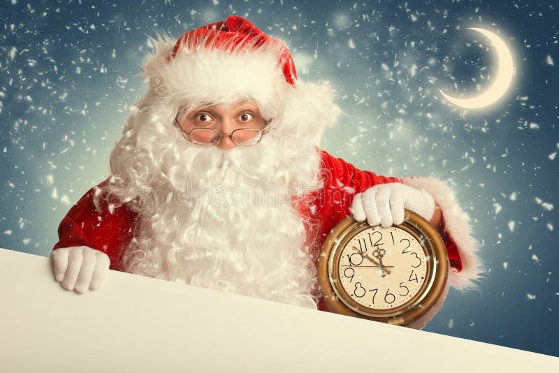 Santa Claus con l'insegna in bianco bianca che tiene un orologio fotografia stock