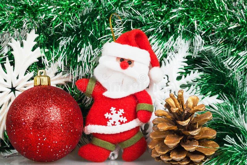 Santa Claus con la bola roja de la Navidad, el topetón y los copos de nieve blancos foto de archivo libre de regalías