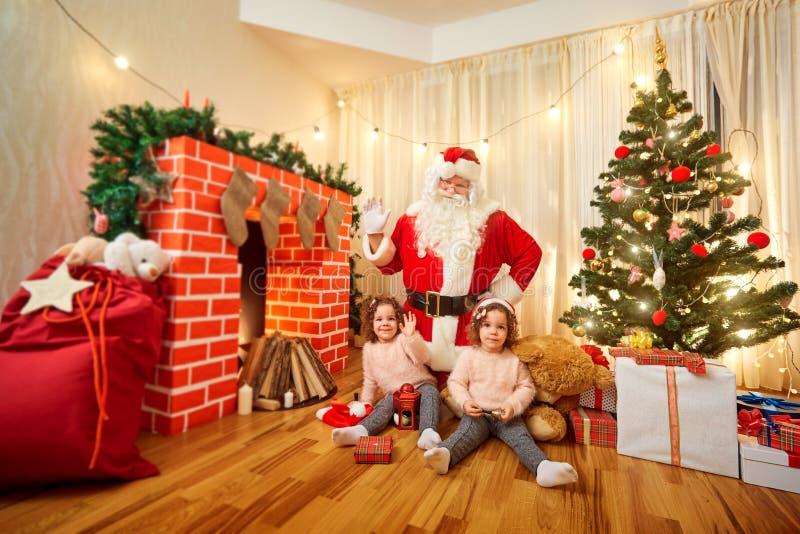 Santa Claus con los niños en el cuarto con el árbol de navidad fotografía de archivo