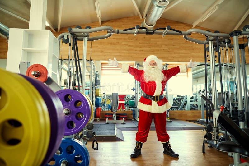 Santa Claus con pesas de gimnasia en el gimnasio para la Navidad imagenes de archivo