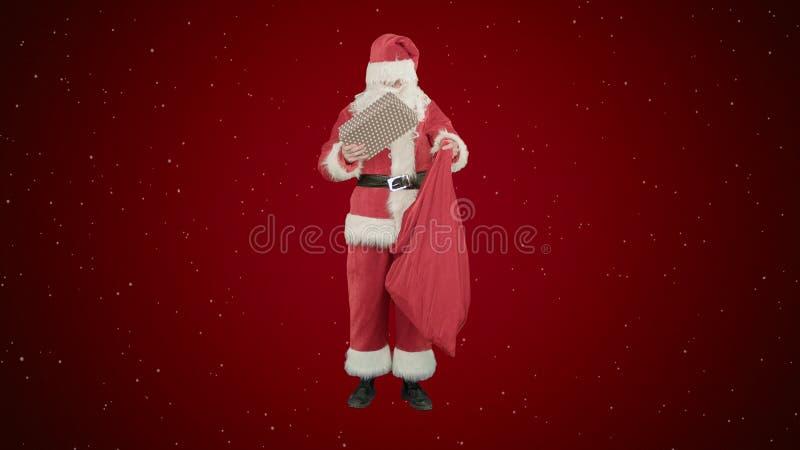Santa Claus con su saco de porciones de presentes en fondo rojo con nieve fotos de archivo