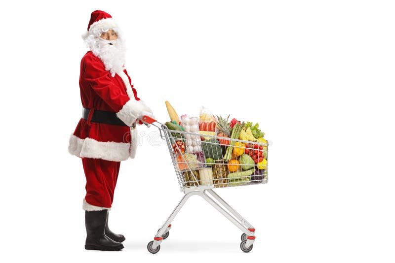 Santa Claus con un carro de la compra por completo de los productos alimenticios imágenes de archivo libres de regalías