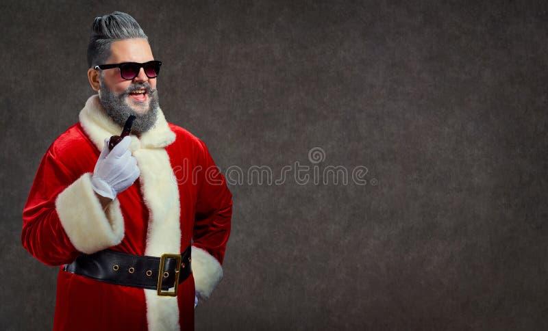 Santa Claus con un peinado y un cigarro lanza un humo feliz fotos de archivo