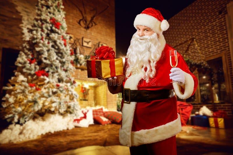 Santa Claus con un regalo a disposición en un cuarto con una chimenea en el Ch foto de archivo libre de regalías