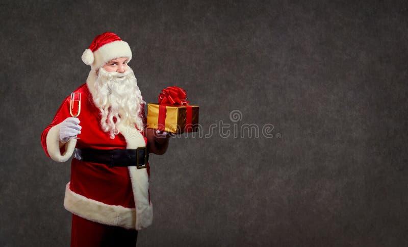 Santa Claus con un regalo y un vidrio de champán imagen de archivo libre de regalías