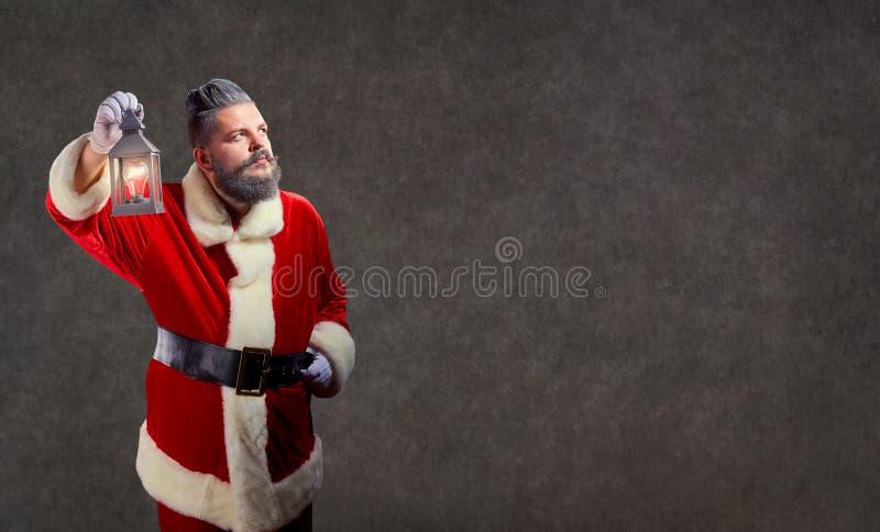 Santa Claus con una lámpara en una Navidad imagen de archivo