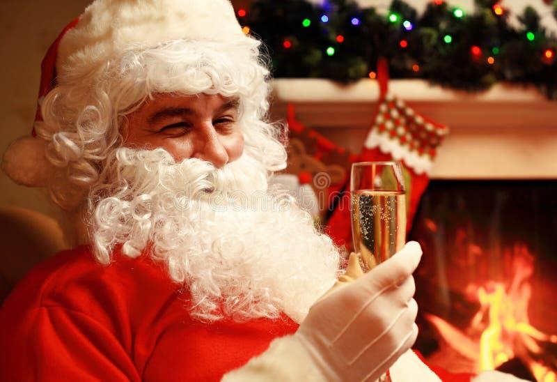 Santa Claus con vetro del champagne del vino spumante vicino ad un albero di Natale fotografia stock