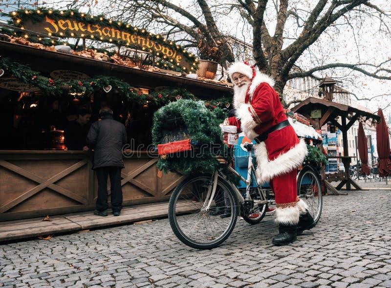 Santa Claus conduz uma bicicleta decorada com os presentes em Munich fotos de stock
