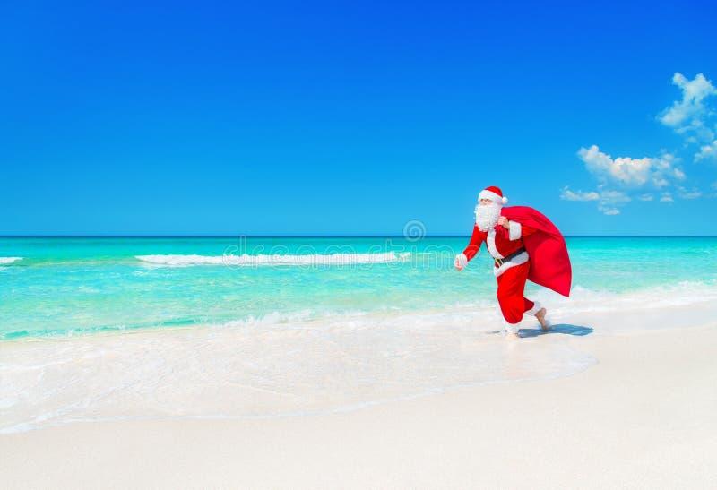 Santa Claus corre ao longo da praia do oceano com o saco dos presentes do Natal fotos de stock