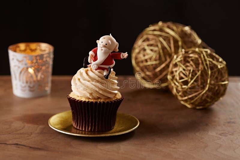 Santa Claus cupcake on Christmas background. Santa Claus cupcake on black Christmas background stock photo