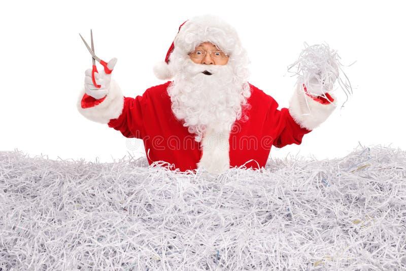 Santa Claus cutting paper with scissors stock image