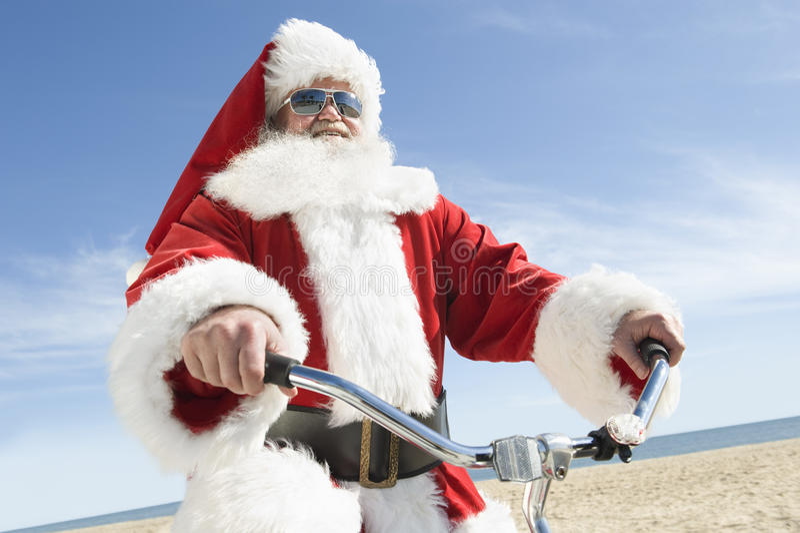 Santa Claus Cycling Against Blue Sky fotos de stock royalty free