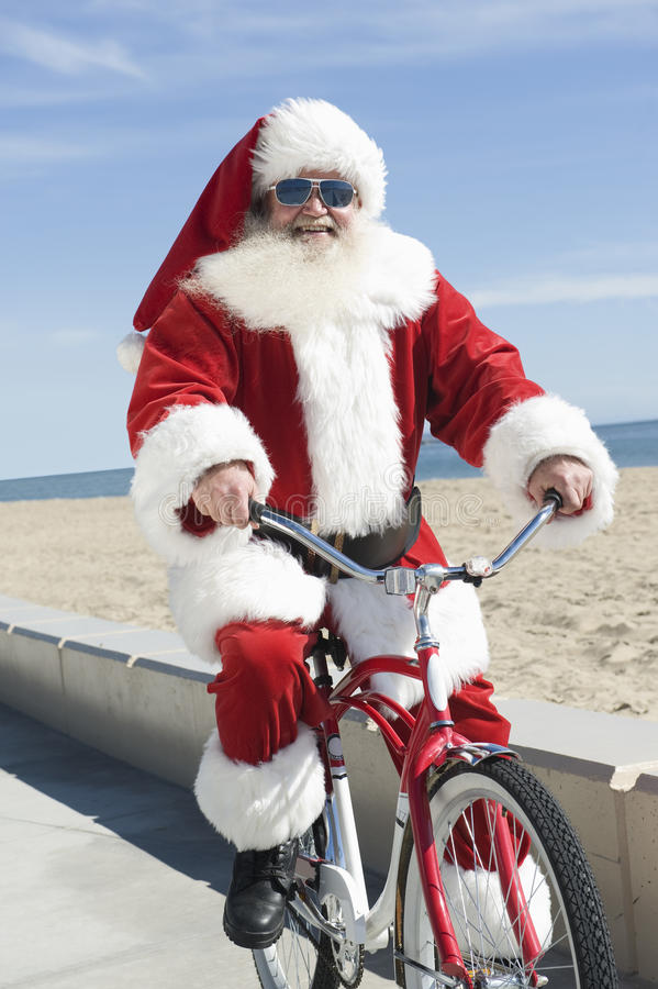 Santa Claus Cycling By Beach fotografie stock libere da diritti