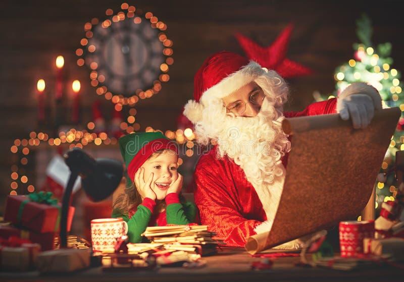 Santa Claus czyta listę dobrzy dzieci mały elf Christm obraz royalty free