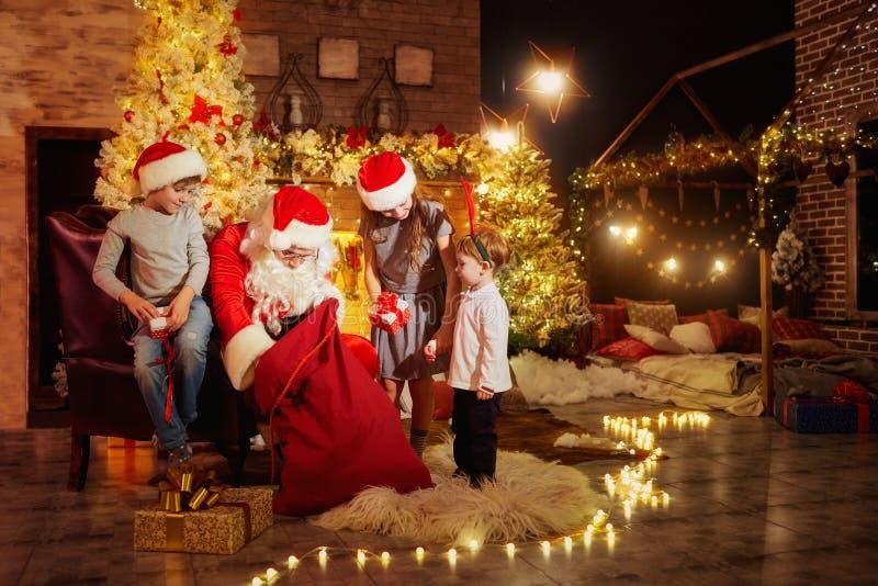 Santa Claus da presentes a los niños el día de la Navidad fotos de archivo