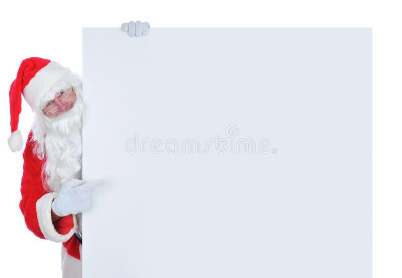 Santa Claus dal lato di ampio manifesto in bianco che indica allo spazio fotografia stock libera da diritti