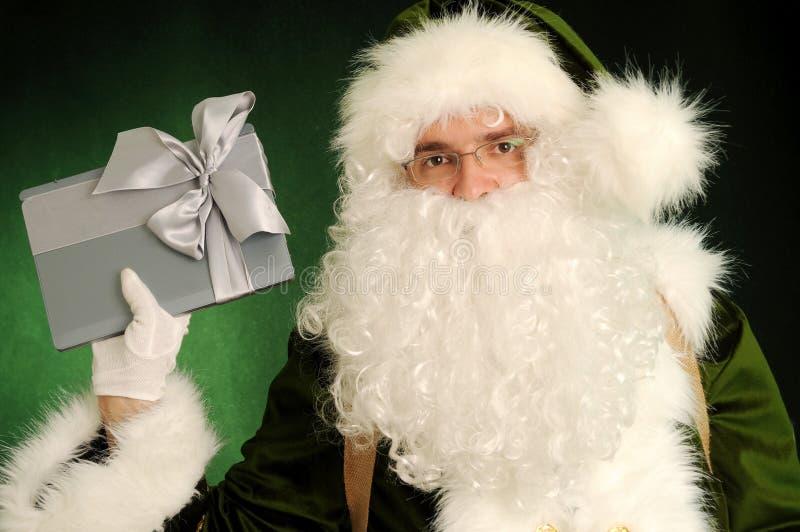Santa Claus dans le costume vert tenant le présent photos libres de droits